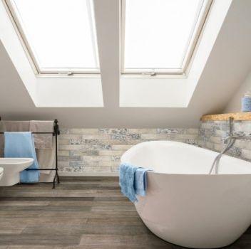 Niebieska łazienka z wanną wolnostojącą, toaletą oraz oknami dachowymi