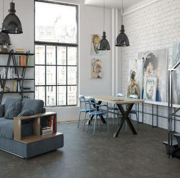 Biały salon z obrazami, drewnianym stołem z niebieskimi krzesłami oraz niebieską kanapą