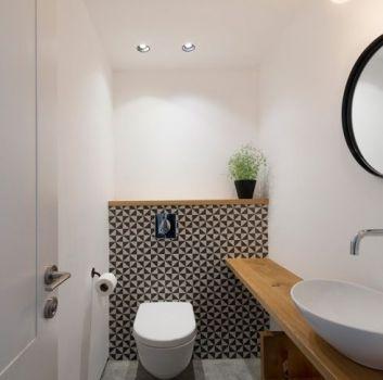 Biało-czarna toaleta z drewnianymi blatami, umywalką nablatową i okrągłym lustrem