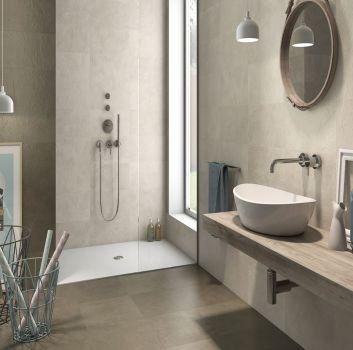 Szara łazienka z prysznicem przy oknie, drewnianym blatem z umywalką nablatową oraz okrągłym lustrem