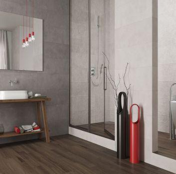 Szara łazienka z wydzieloną częścią kąpielową w której jest wanna wolnostojąca i prysznic oraz drewnianym stolikiem z umywalką nablatową