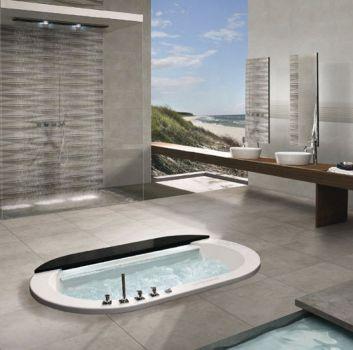 Szara łazienka z zabudowaną pośrodku wanną, dużym prysznicem pod ścianą oraz ogromnym oknem w rogu