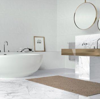 Biało-szara łazienka z wanną wolnostojącą, złotym blatem z dwoma wbudowanymi umywalkami oraz złotymi lustrami