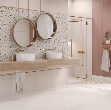 Łazienka z dwoma umywalkami nablatowymi, dwoma okrągłymi lustrami, białą wanną i toaletą oraz płytkami lastryko hika