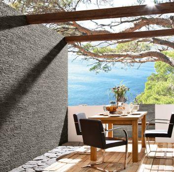 Taras z widokiem na ocean z zastawionym drewnianym stolikiem, trzema fotelami i kamieniem dekoracyjnym