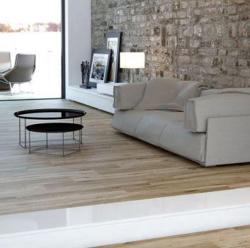 Duży salon z płytkami drenwopodobnymi i kamienną ścianą