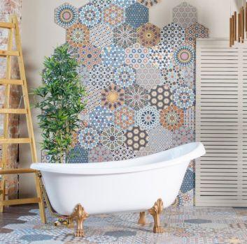 Łazienka z białą wanną wolnostojącą, drabiną i parawanem oraz kolorowymi płytkami