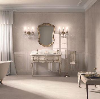 Beżowa łazienka w stylu vintage z białą, owalną wanną z ozdobnymi nogami, złotą baterią retro wolnostojącą, ozdobnym sekretarzykiem z umywalką i lustrem w ramie, stojącym wieszakiem z ręcznikiem, siedziskiem z tacą, żyrandolem, kinkietami w kształcie świe