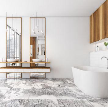 Biała łazienka z drewnianymi akcentami, białą owalną wanną z baterią wolnostojącą, wiszącą półką z dwiema białymi umywalkami i dwoma wysokimi, wąskimi lustrami oraz płytkami imitującymi marmur na podłodze