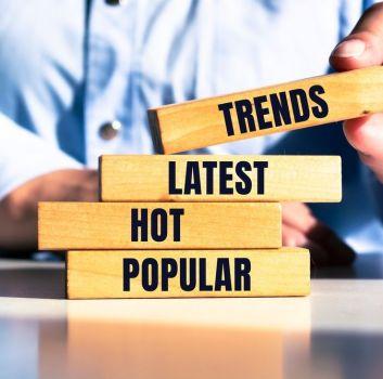 Zdjęcie z czterema klockami z napisami po angielsku trends, latest, hot, popular, a w tle mężczyzna w niebieskiej koszuli