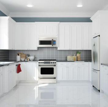 Biała kuchnia z szafkami stojącymi i wiszącymi, lodówką, piekarnikiem, zlewem z baterią pod oknem, niebieską ścianą pod sufitem, szarymi cegiełkami między meblami i błyszczącymi płytkami na podłodze