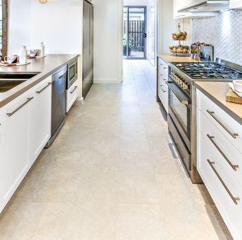 Jasna kuchnia z białymi meblami z drewnianymi blatami tworzącymi korytarz, ze srebrnymi sprzętami jak zmywarka, kuchenka, lodówka, zlewozmywak oraz ze sprzętami kuchennymi i dodatkami