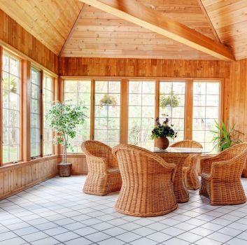 Piękny zakryty taras z drewna z licznymi oknami, stołem ze szklanym blatem, wiklinowymi fotelami, kwiatami w donicach i białymi płytkami na podłodze z ciemną fugą